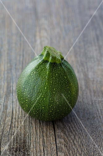 A round, green Eight Ball courgette