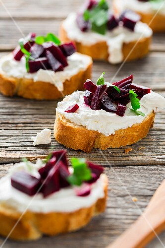 Slices of baguette topped with goat's cheese, marinated red turnip and parsley