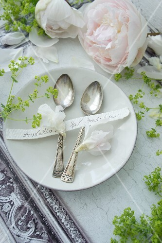 Place setting with silver spoons, name tag and peonies