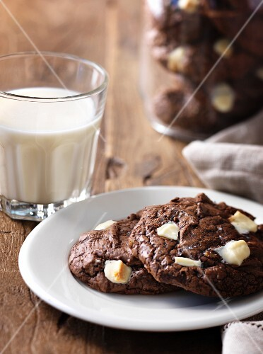 Chocolate cookies with white chocolate chips and a glass of milk
