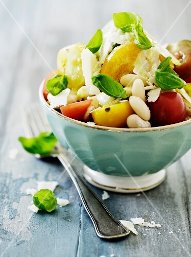 A colourful tomato salad with white beans, basil and Parmesan cheese