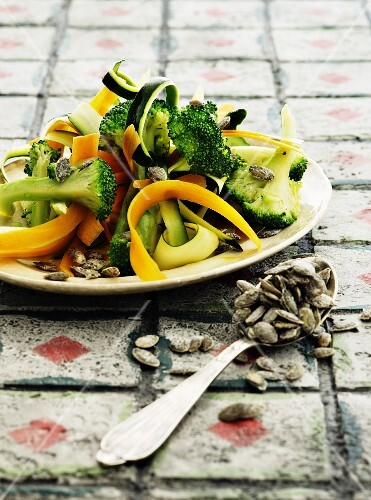 Vegetable salad with broccoli, pumpkin seeds and courgette and carrot strips