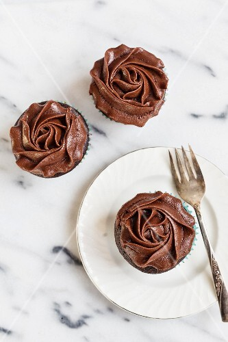 One chocolate and chai cupcake on a plate with a fork with two next to it