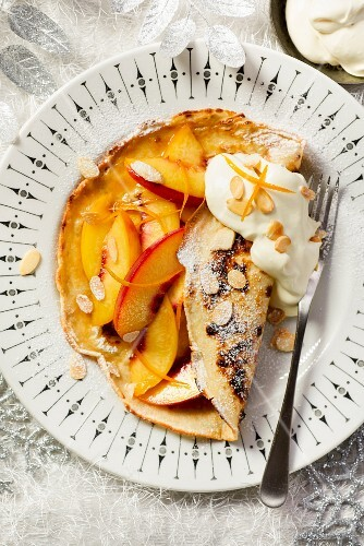 Peach pancakes with orange zest and flaked almonds
