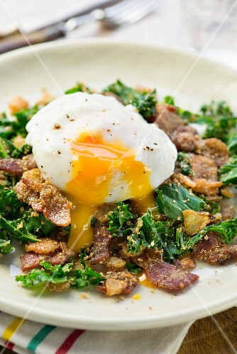 A poached egg with bacon and kale