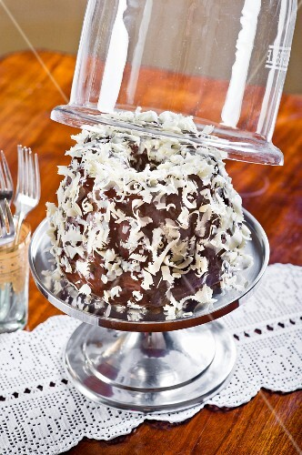 A 'Snow' Bundt cake on a cake with a glass cloche