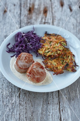 Pork medallions with a creamy mustard sauce served with a potato and apple cakes and red cabbage