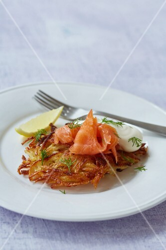 A potato fritter with salmon, crème fraîche and dill