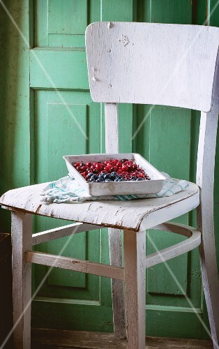Blackberries and lingonberries on a vintage tray on an old white wooden chair against the green wooden wall