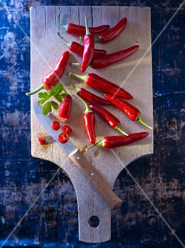 Red chilli peppers on a wooden board with flat leaf parsley