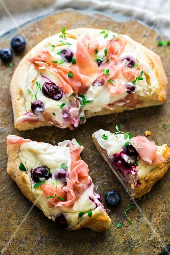Pizza with goat's cream cheese, ham and blueberries