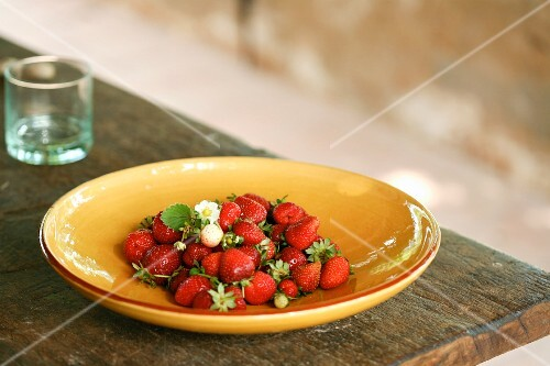 Freshly picked strawberries on a plate on a wooden table outside