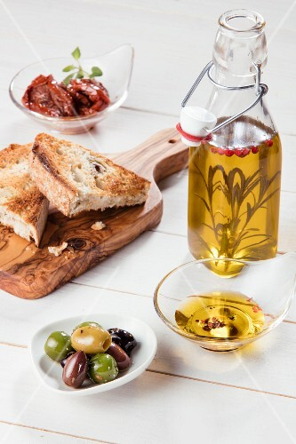 Antipasti: olives, dried tomatoes, olive oil and grilled bread (Italy)