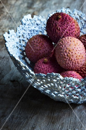 Lychees in a grey handmade basket on a wooden surface