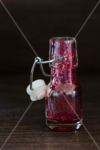An empty bottle with the remains of beetroot smoothie