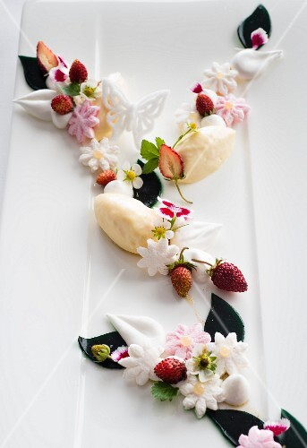 White chocolate mousse with wild strawberries and sugar flowers