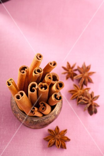 Cinnamon sticks and star anise on a pink surface