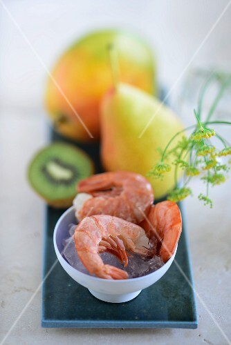 Prawns on ice with a mango, a pear and a kiwi in the background