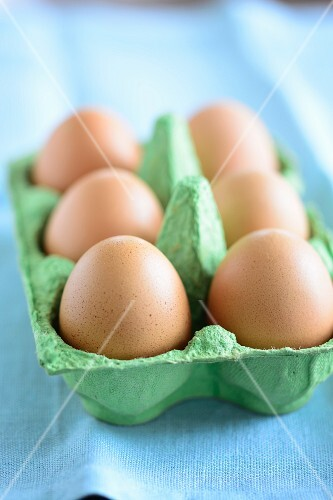 Six brown eggs in an egg box