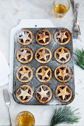 Homemade mince pies decorated with a star dusted with icing sugar in a baking tin