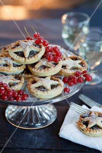 Homemade mince pies with star lids and icing sugar on a cake stand with redcurrants