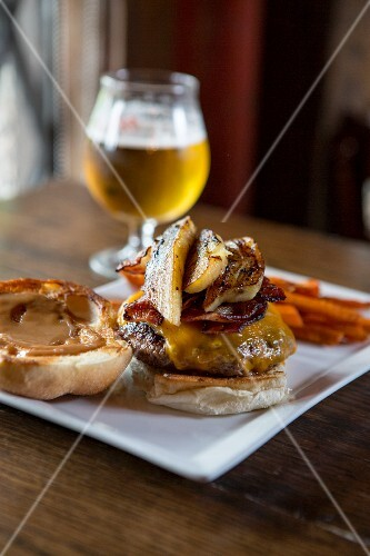 Cheeseburger with bacon and grilled bananas served with sweet potato fries and a glass of beer