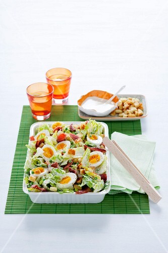 Caesar salad with bacon, hard-boiled eggs and croutons