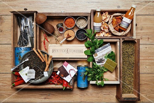 Various spices, herbs, dried fruit and kitchen utensils in wooden boxes
