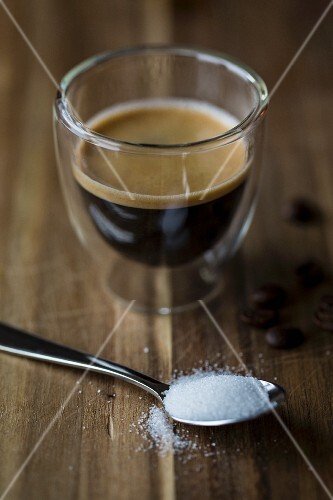 A glass of espresso with a spoonful of sugar