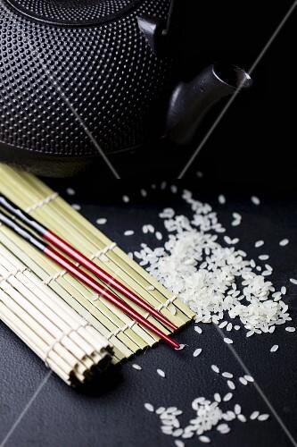 An arrangement featuring chopsticks, a bamboo mat, a teapot and rice (Asia)