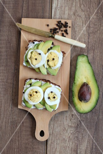 Slices of bread topped with avocado, egg and peppercorns
