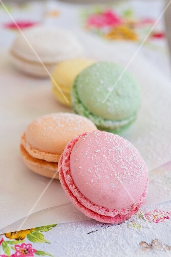 Various macaroons on paper with icing sugar (close-up)