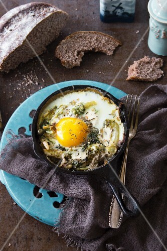A fried egg with herbs and pine nuts