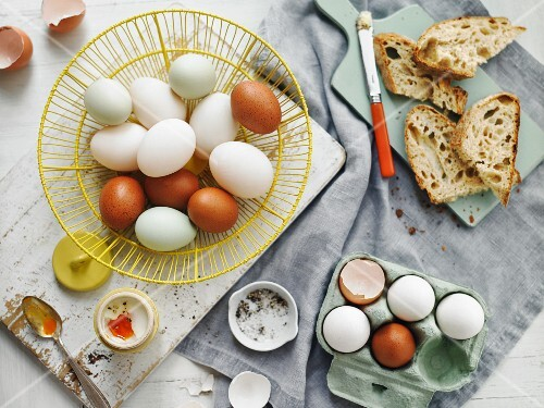 Brown and white eggs in a basket and in an egg box