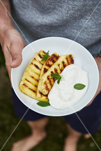 A man holding a plate of grilled pineapple and quark cream