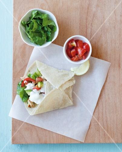 A burrito with avocado, tomatoes, lettuce and sour cream