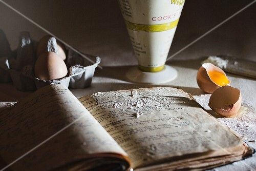 A baking scene with and old recipe book, eggs and flour