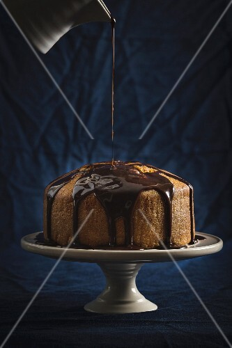 Chocolate glaze being poured over a cake