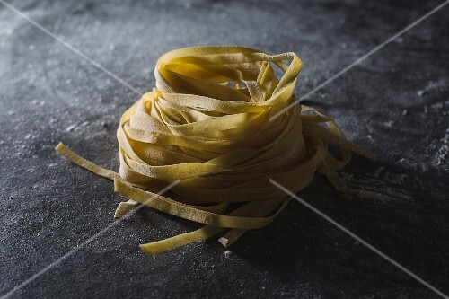 Homemade tagliatelle on a dark surface