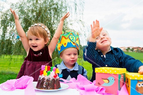 Three small children at a birthday party in a garden