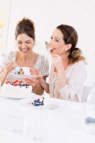 Two women eating berry cream cake