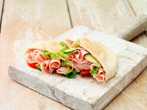 Pita bread filled with wafer thin ham, lettuce, tomatoes and cucumber