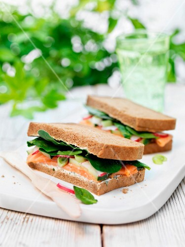 A black bread sandwich with salmon, spring onions, radishes and spinach