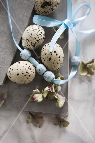 Easter still-life arrangement of quail eggs, beads on ribbon & hydrangea florets