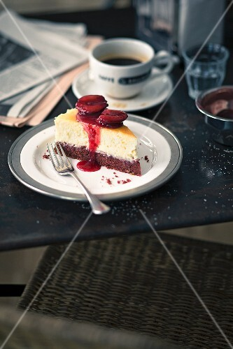A slice of Red Velvet cheesecake with plums