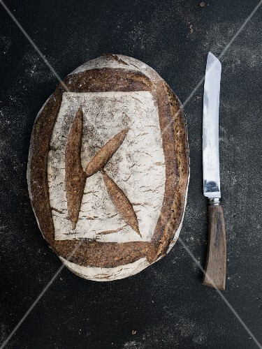 A whole loaf of sourdough rye bread next will bread knife (seen from above)