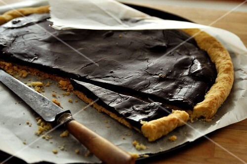 Chocolate tart, sliced, on a piece of baking paper