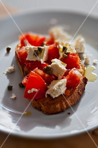 A slice of bread topped with tomatoes, feta cheese and capers