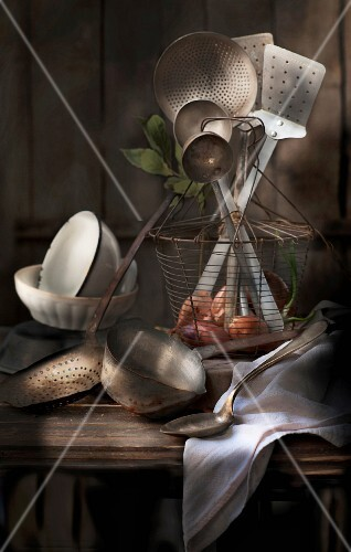 Old kitchen utensils in a wire basket and next to it on a wooden table