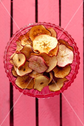 Homemade apple chips in a glass bowl (seen from above)